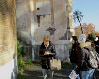 La prof.ssa Tiziana Di Crescenzo sotto la lapide che riporta la palla di cannone ritrovata tra i resti di alcune macerie della Chiesa di San Pietro Montorio