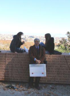 Enrico Luciani ripreso tra due alunne solitarie con vista sul panorama di Roma
